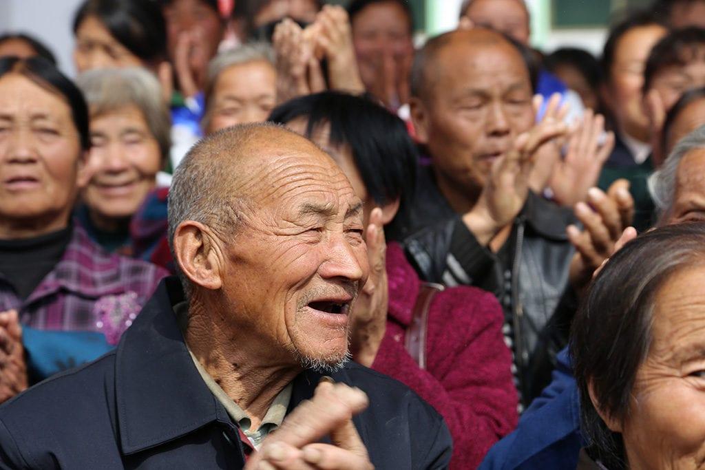 Eldre mann klapper i forsamlingen på gudstjeneste i Kina