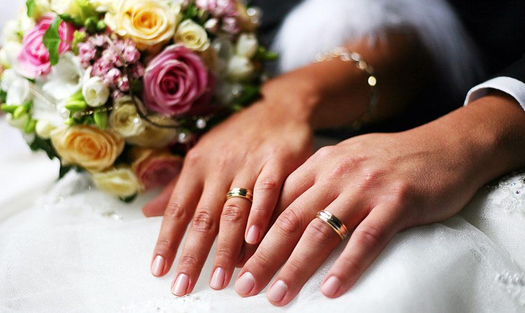 Hender til nygift par med gifteringer, brudebukett
