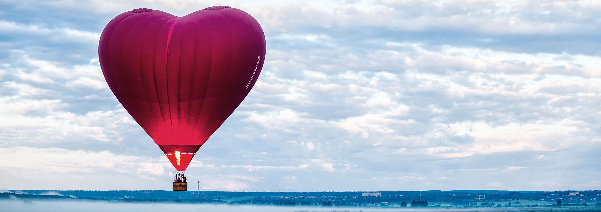 Rød luftballong formet som et hjerte svever i landskap