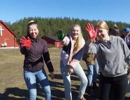 Ungdom som vinker med maling på hendene utenfor Vegårtun