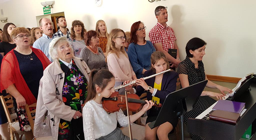 Gudstjeneste i Polen, sang akkopagnert av fiolin, tverrfløyte og piano