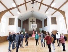 Basecamp deltakere i kirkesal med basketballbane