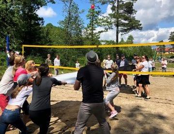 Folk som kaster vannballong over volleyball-nett