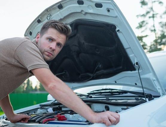 Foto av mann med åpent panser på bilen.