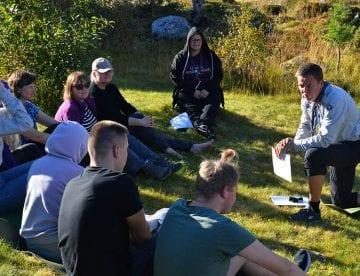 Speidere får undervisning ute på gresset i sola