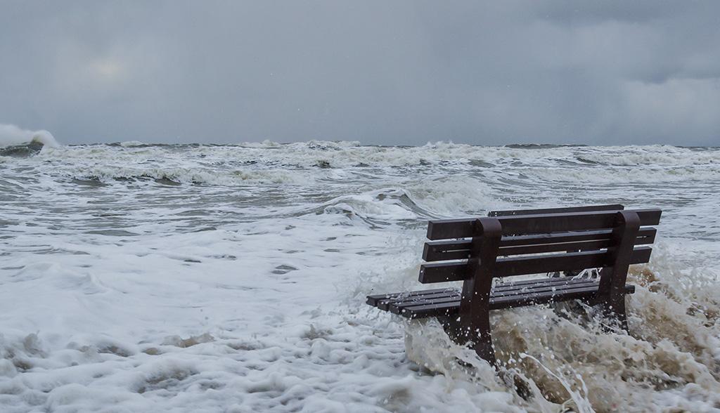 Sittebenk omgitt av brusende hav