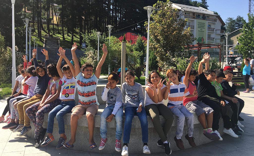 Barn og ungdom sitter på en fontene