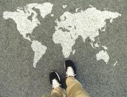 Verdenskart på asfalt, med føtter ovenfra og ned