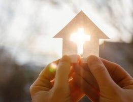 Hender som holder et hus laget av papir, med et kors i midten hvor sollyset skinner gjennom.