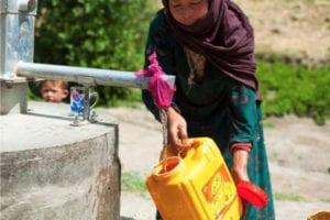 Kvinne fyller på en vanntank