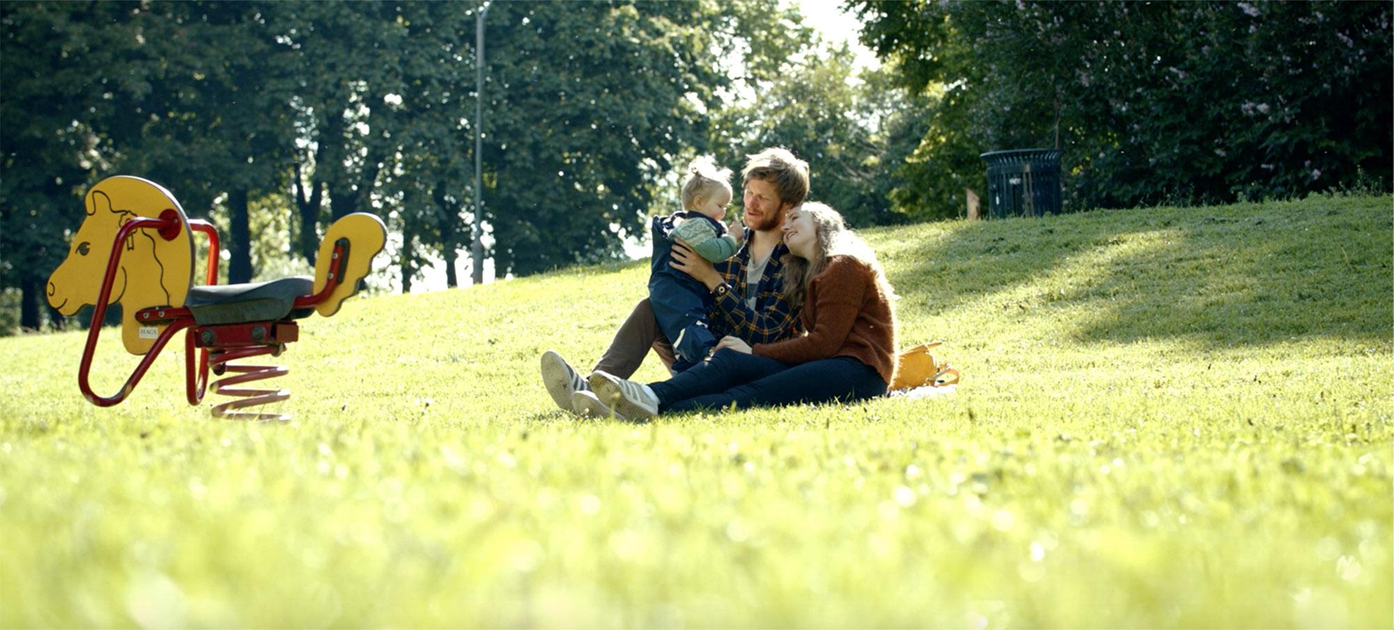 Unge foreldre med et barn på fanget, ute på grønt gress