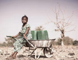 Foto av jente med trillebåre og vannkanne i tørt land.