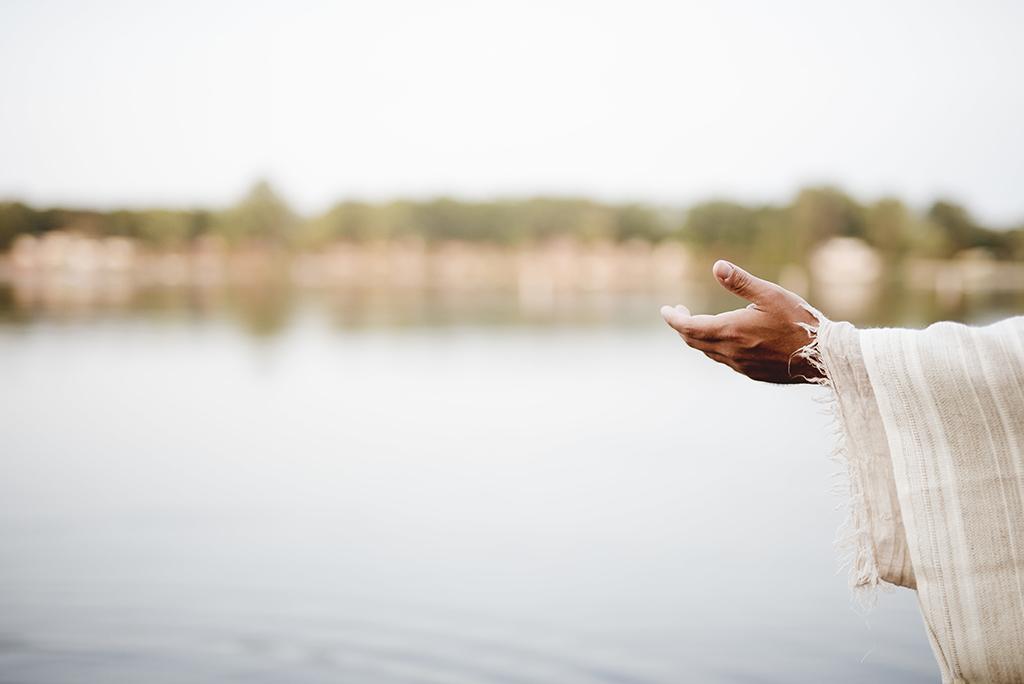Jesus rekker ut en hånd. Vann i bakgrunnen.